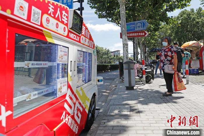 无人餐车停靠在地铁出入口,吸引了市民的目光。 殷立勤 摄